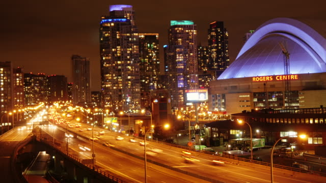 night time timelapse shot of toronto overlooking gardiner expressway. rogers center and highrise buildings. long exposure. - toronto stock videos & royalty-free footage