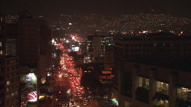 ws ha night time view of traffic in streets and twinkling lights in distant hills / metropolitan district of caracas, miranda, venezuela - caracas stock videos & royalty-free footage
