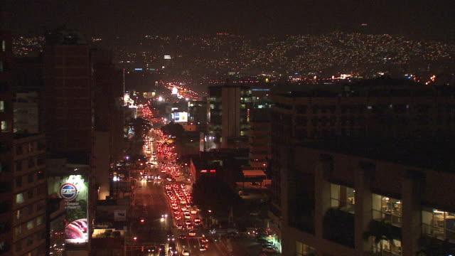 WS HA Night time view of traffic in streets and twinkling lights in distant hills / Metropolitan District of Caracas, Miranda, Venezuela