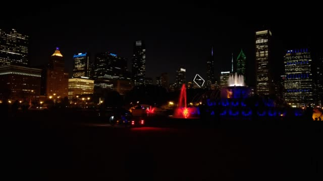 night time views of buckingham fountain and the chicago skyline. people visit the fountain and take photos, pedicabs and pedestrians move along. a... - buckingham fountain stock videos & royalty-free footage