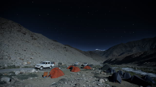 night timelapse of camping under the stars at a campsite in the himalayas - tent stock videos & royalty-free footage