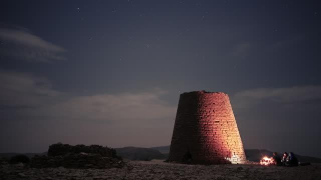 vídeos y material grabado en eventos de stock de night time-lapse of group of travelers camping at a ancient tomb tower in oman - omán