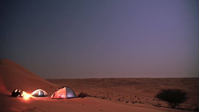 night time-lapse of group of travelers camping in wahiba sand desert in oman - campeggiare video stock e b–roll