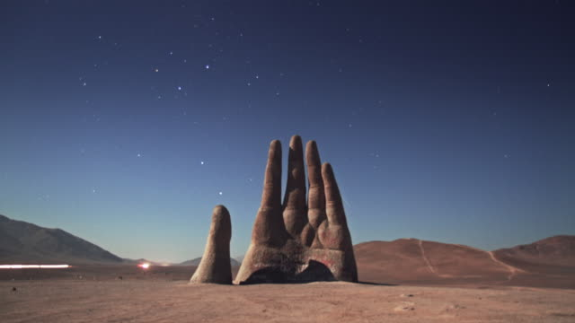 night time-lapse of hand stone statue in the atacama desert with stars and cars moving - atacama region stock videos & royalty-free footage
