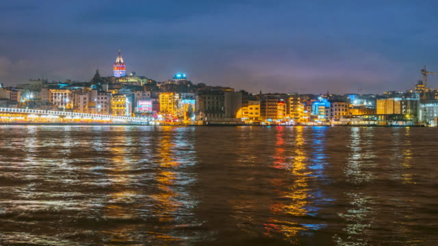 night timelapse of istanbul cityscape galata tower with floating tourist boats in bosphorus ,istanbul turkey - yeni cami mosque stock videos and b-roll footage