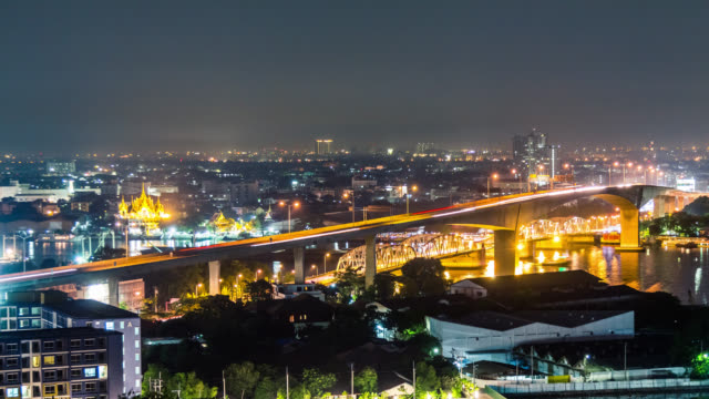 vídeos de stock, filmes e b-roll de night timelapse of the bridge over chaj phraya river with car traffic in bangkok, thailand - rio chao phraya