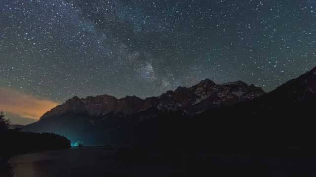 vídeos de stock e filmes b-roll de t/l night timelapse of zugspitze mountain, lake eibsee and the milky way in garmisch-partenkirche, bavaria, germany - astronomia