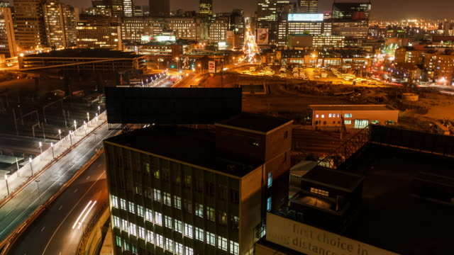 night timelapse shooting down between buildings onto a street with peak traffic, buildings and a taxi rank in the city centre of johannesburg, south africa - taxi rank stock videos & royalty-free footage
