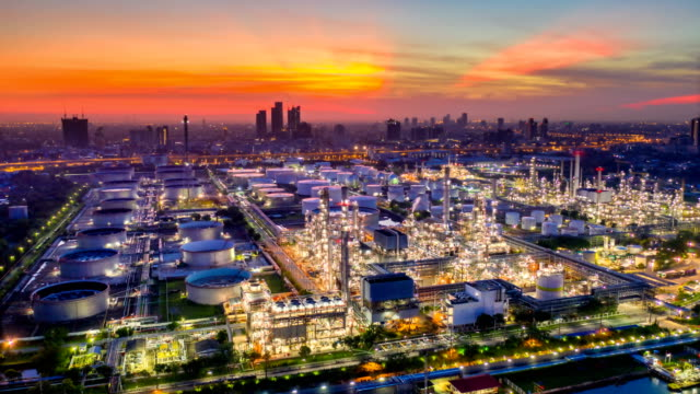 night to day 4k timelapse or hyperlapse of aerial of industrial park with oil refinery and storage tank in asia at sunrise - industria petrolifera video stock e b–roll