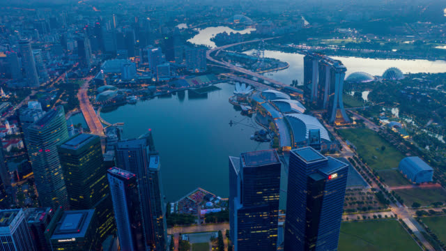 night to day hyperlapse or dronelapse scene of singapore business district downtown at sunrise - marina bay sands stock videos and b-roll footage