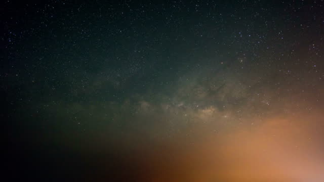 night to day shot of milky way galaxy and mountains - esposizione lunga video stock e b–roll
