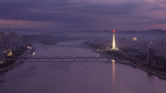 night to day shot of skyline of pyongyang north korea, drpk. wide shot from above on a cloudy day. juche tower,  taedong river. - spoonfilm stock videos and b-roll footage