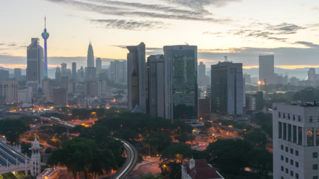 Night to day sunrise at Kuala Lumpur city skyline. Tilt up.