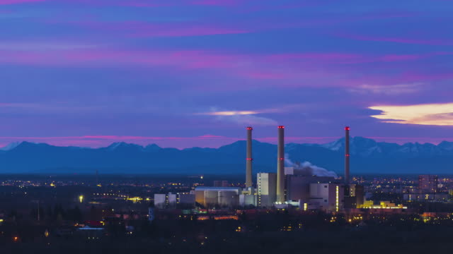 t/l night to day sunrise overlooking the power plant in munich with the bavarian alps in the background - very colourful clouds - bavarian alps点の映像素材/bロール