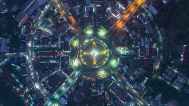 vídeos de stock, filmes e b-roll de night to day time lapse or hyper lapse : aerial top view highway road roundabout or intersection, circle at night for transportation, distribution or futuristic background. - junção de rua ou estrada