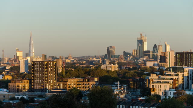 a night to day timelapse transition looking across residential flats and offices towards the city of london as morning arrives and the sun rises shadows travel across the buildings and trees - day stock videos & royalty-free footage