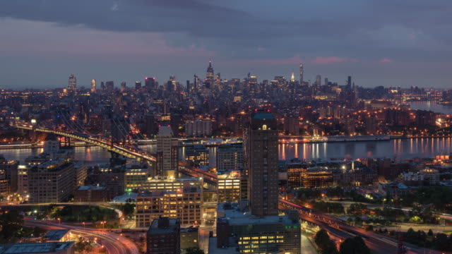 night to day transition / sunrise time lapse (slow zoom out) unique view from a rooftop in downtown brooklyn overlooking the east river showing manhattan skyline including landmarks such as manhattan bridge, williamsburg bridge, empire state building. - williamsburg bridge stock videos and b-roll footage