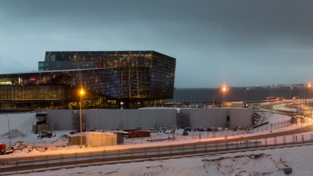 A night to day winter time lapse from central Reykjavik, Iceland, featuring the Harpa Concert Hall with vehicle traffic and construction in the foreground