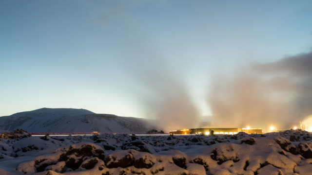 A night to day winter time lapse of the buildings surrounding the Blue Lagoon geothermal spa in Iceland featuring a mix of low, fast moving clouds overhead and thick steam rising from below