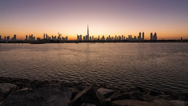 night to day/time lapse dubai skyline at sunrise / dubai, uae - moving activity stock videos & royalty-free footage