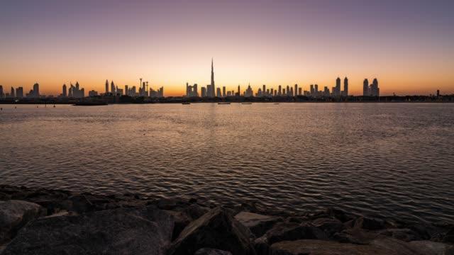 night to day/time lapse dubai skyline at sunrise / dubai, uae - dubai stock videos & royalty-free footage