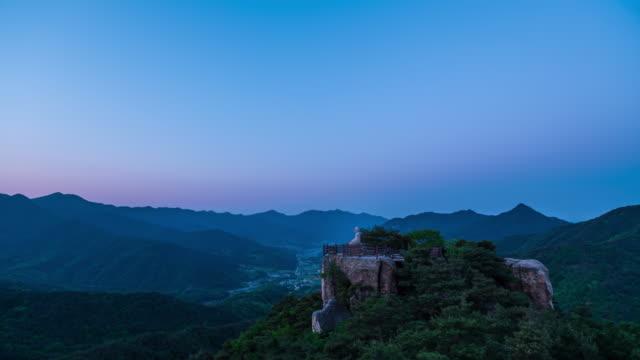 night to morning view of stone seated buddha at yongseondae cliff of gwallyongsa temple and hwawangsan mountain / changnyeong-gun, gyeongsangnam-do, south korea - romantic sky stock videos & royalty-free footage