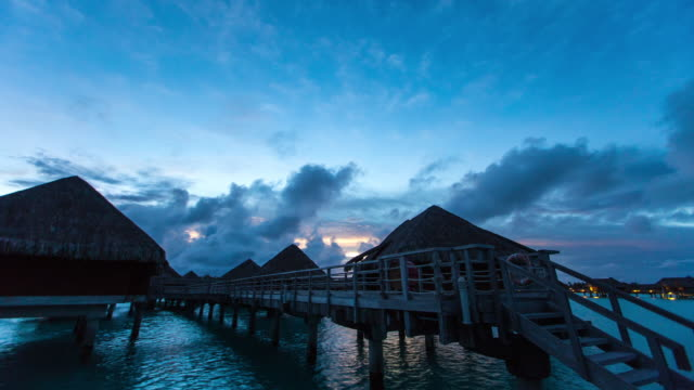 night to morning view of the sea and bungalow - bora bora stock videos & royalty-free footage