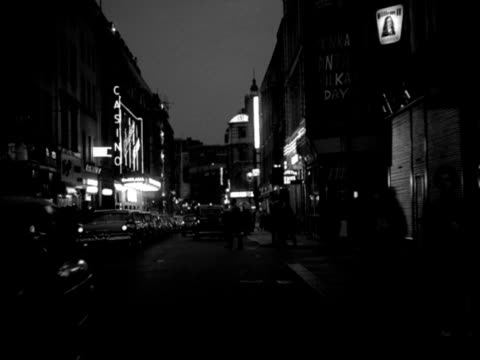 vídeos y material grabado en eventos de stock de night tracking shot backwards from the top of a car along old compton street soho moving past shops and theatres with neon lights - soho londres