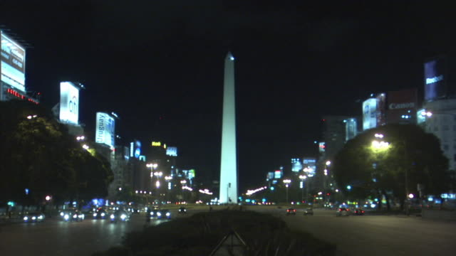ws night traffic on 9 de julio avenue with the obelisk in background, buenos aires, argentina  - avenida 9 de julio video stock e b–roll