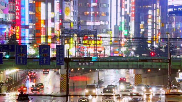 night traffic road and crowded with banner sign on tall building in the city while raining - road signal stock videos & royalty-free footage