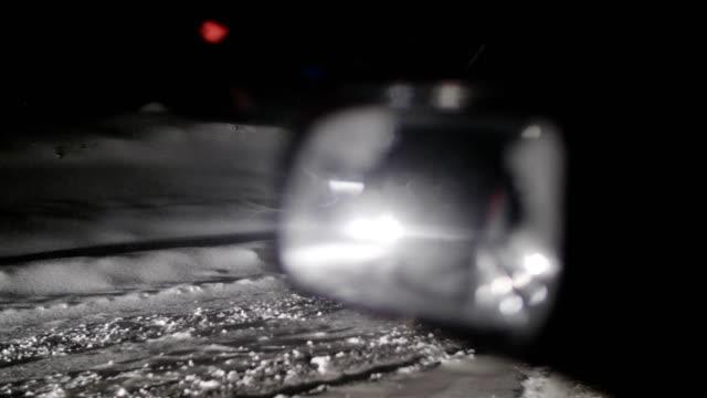 nachtreise. fahren auf schneebedeckter straße in der nacht, stecken auf der straße mit dem ersten schnee fallen. wetterverzögerung bei einem wintersturm. blizzard in den bergen. - innenspiegel stock-videos und b-roll-filmmaterial