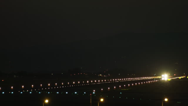 LS night, twin-engine jet taking off at night, camera tracks aircraft into flight,  front view, RED R3D 4K