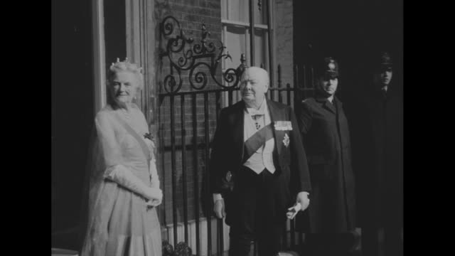 UK Prime Minister Winston Churchill stands in doorway of 10 Downing Street with wife Clementine behind he wears sash of the Order of the Garter and a...