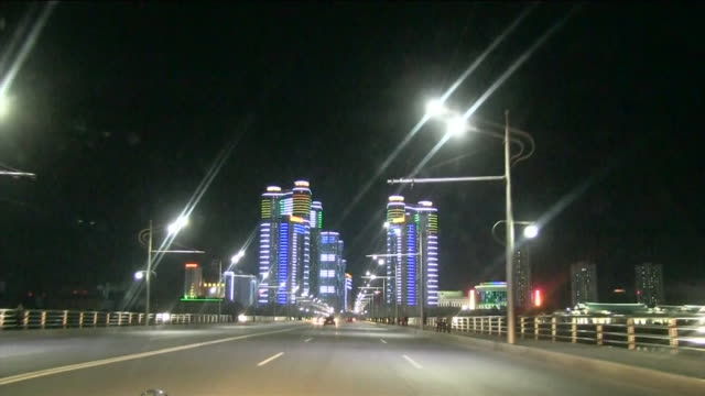 Night view Car Point Of View of Pyongyang city at night Skyscrapers glowing in various colors seen far in the distance Car turning a corner driving...