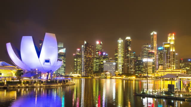 Night view of central Singapore Harbor with skyscapers and museum in Singapore.