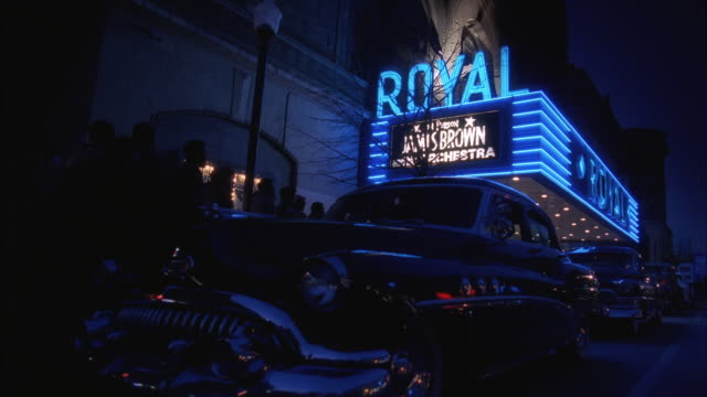 WS Night view of crowds outside theater with 1950's cars