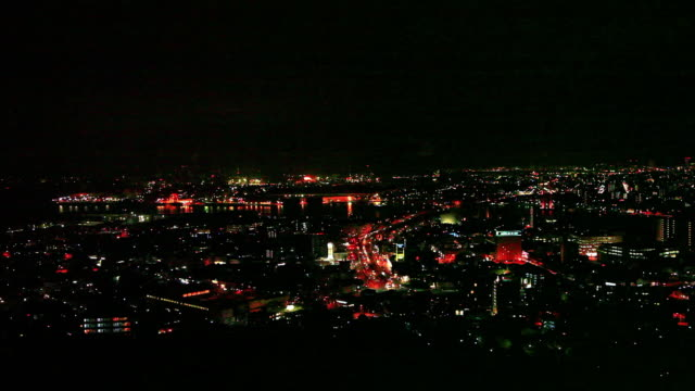 vidéos et rushes de night view of kitakyushu city seen from the observation deck of takatoyama park; town area and a group of industrial plants colored red, orange,... - phare de véhicule