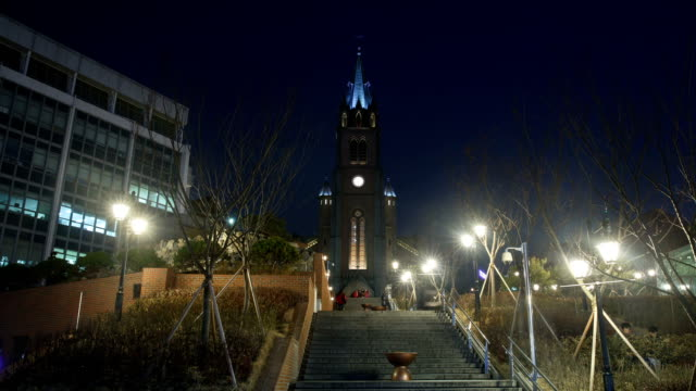 Night view of people going up and down on the steps at Myeong Dong cathedral