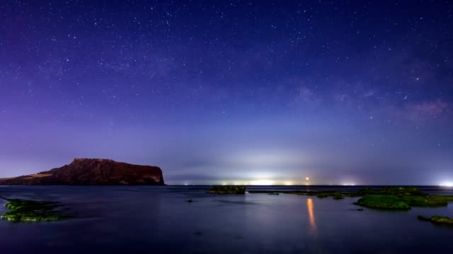 night view of seongsanilchulbong hill (famous place for sunrise) and milky way in seogwipo, jeju island - hill点の映像素材/bロール