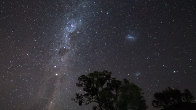 night view of stars diurnal motion and magellanic clouds in milk way in canberra, australia - a forma di stella video stock e b–roll
