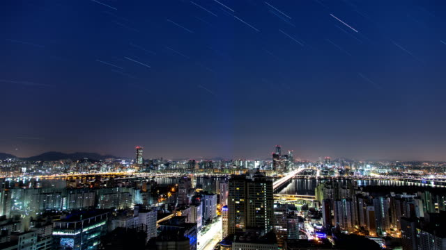 night view of stars over the yoeuido financial district in seoul - sternenspur stock-videos und b-roll-filmmaterial