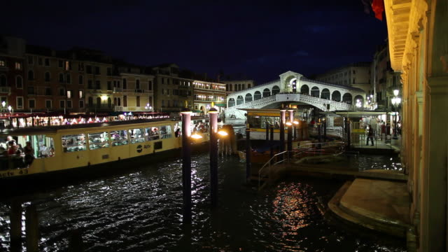 WS Night view of vaporetto mooring to jetty on Grand Canal with Rialto Bridge in background / Venice, Italy