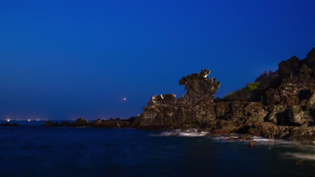 night view of yongduam rock(it is a volcanic rock formation in the form of a dragon's head) and sea in seogwipo, jeju island - 巨礫点の映像素材/bロール