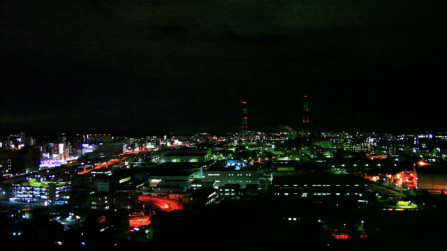 vidéos et rushes de night view seen from the observation deck of takatoyama park; illumination of town area and industrial plants; street lights; car headlights: long... - phare de véhicule