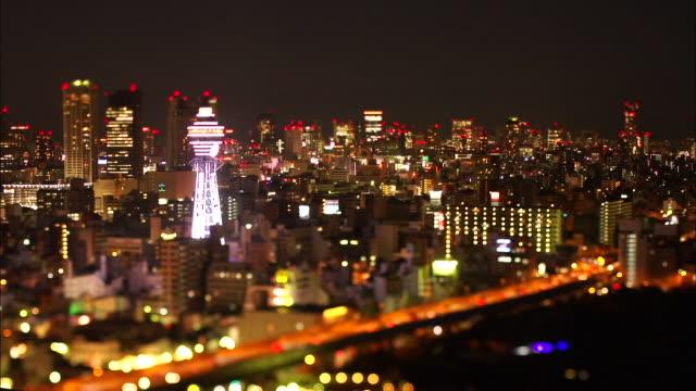 night view with illuminated tsutenkaku tower, osaka, japan - präfektur osaka stock-videos und b-roll-filmmaterial