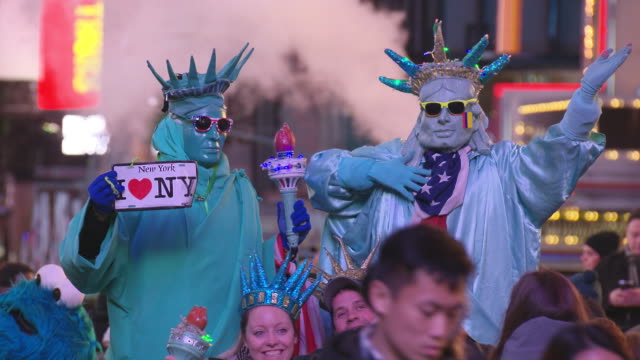 night vision crowded times square statue of liberty street performers stand above the crowd holding a torch in their hands mcdonalds in the... - performer stock videos & royalty-free footage