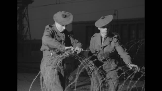 """military personnel, probably british, remove razor wire near a facility; nearby sign in german translates loosely to """"attention! this is not... - 丸くなる点の映像素材/bロール"""
