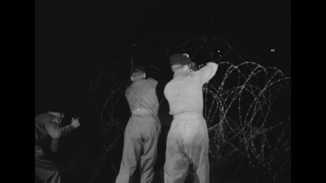 soldiers wearing berets with pom-poms atop un-string, cut, wrap coiled razor wire as they remove it from an area; vs coils of wire / note: exact year... - 丸くなる点の映像素材/bロール