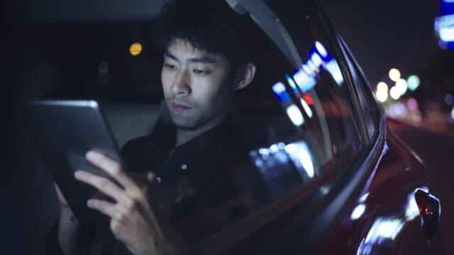 vídeos de stock, filmes e b-roll de noite jovem usando laptop enquanto viajava no carro - asiático