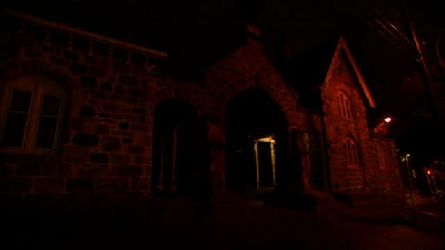 vídeos y material grabado en eventos de stock de 1080i hd: stone greek revival gatehouse & sexton's residence, car headlights shining across front of building, slight no people. - ann arbor